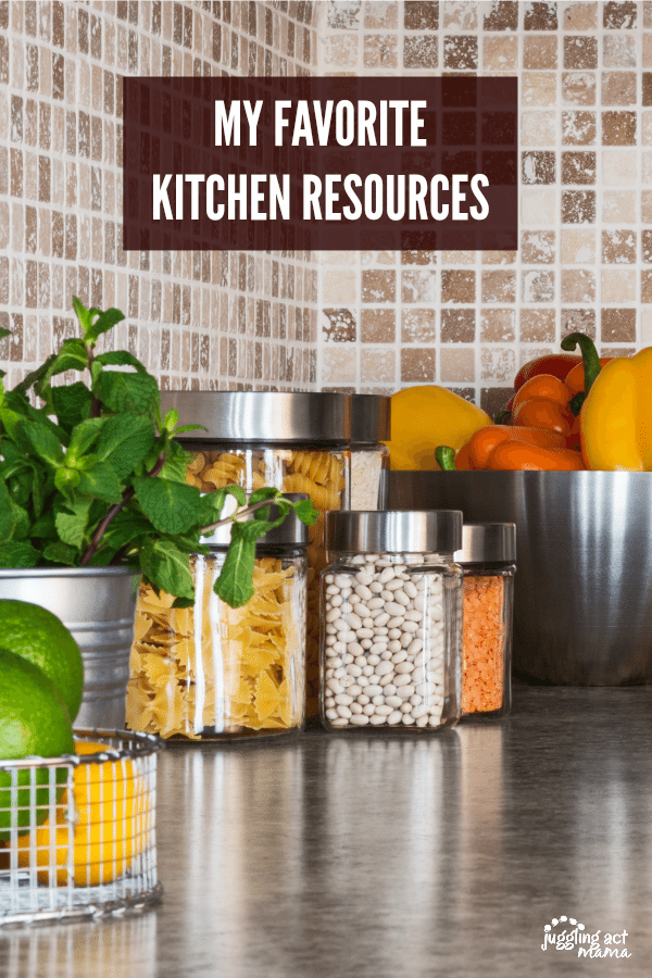 Kitchen Resources Featured Image - A grey countertop with pantry staples like pasta and beans in clear jars with silver lids. A large silver bowl filled with red, orange and yellow peppers. A pot of fresh mint. A baskete of limes and lemons.