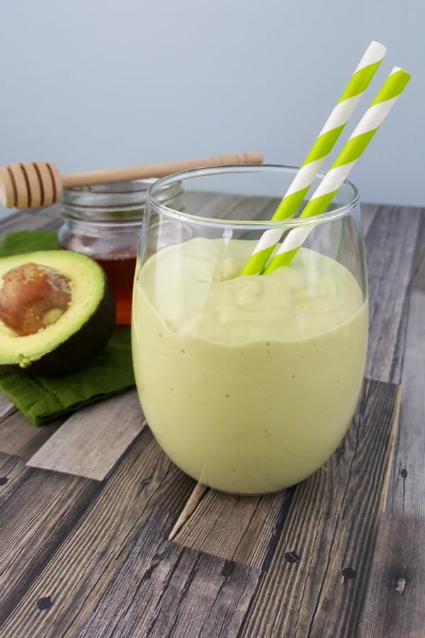 How to Make Homemade Smoothies - close up of Avocado and  Banana Smoothie with green and white straws.