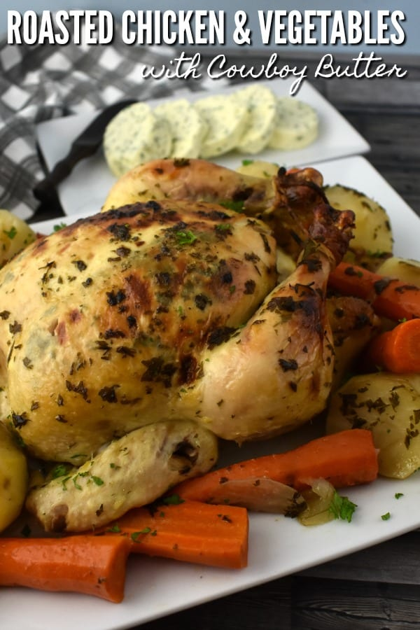 Delicious Roasted Chicken on a platter with potatoes and carrots.
