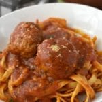 Authentic Italian Meatballs topping a bowl of spaghetti with sauce.