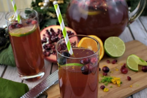 close up of Pomegranate Punch in a glass pitcher along with tall glasses of punch garnished with fresh limes, oranges, cranberries and pomegranate seeds.