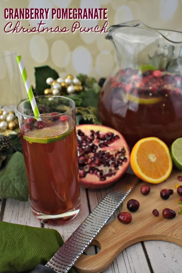Pomegranate Punch in a glass pitcher along with tall glasses of punch garnished with fresh limes, oranges, cranberries and pomegranate seeds.