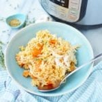 Instant Pot chicken and rice recipe- a blue bowl with brown rice, shredded chicken and sliced carrots next to an Instant Pot