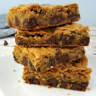 A stack of chocolate chip cookie bars on a white plate with a blue towel in the background.