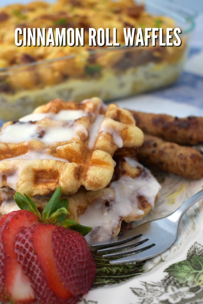 Cinnamon Rolls Waffles drizzled with icing with breakfast sausage and a cut strawberry and a fork. A breakfast casserole sits in the background.