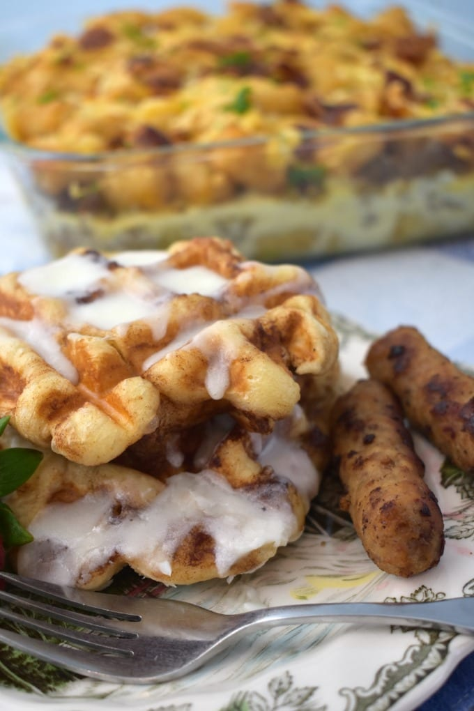 Cinnamon Rolls Waffles drizzled with icing with breakfast sausage and a fork. A breakfast casserole sits in the background.