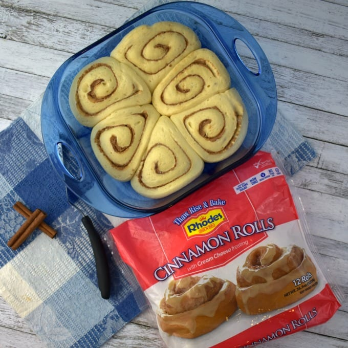 A baking dish with cinnamon roll dough sits on a table with a package of Rhodes Bread cinnamon rolls and a blue and white checked towel.