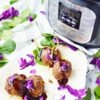 Korean Meatballs in a soft taco shell with purple cabbage. An Instant Pot Pressure cooker is seen in the background.