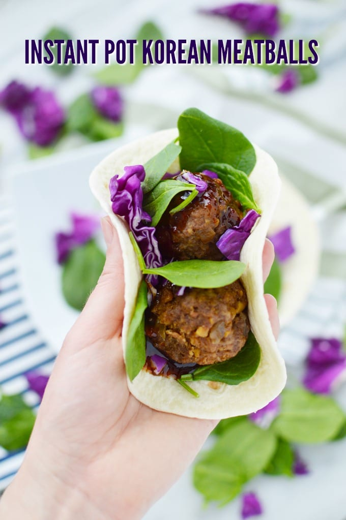A hand holds a soft flour tortilla stuffed with spinach, Korean Meatballs and purple cabbage.
