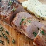Slices of oven roasted pork tenderloin on a cutting board with a sprig of fresh thyme. In the background are slices of compound butter and ramekins with salt and pepper