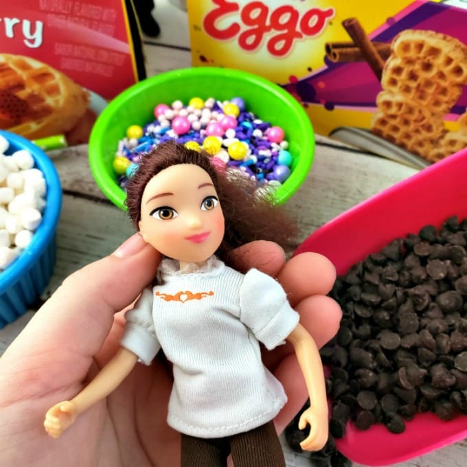 A child's hand holds the Lucky doll from Spirit Riding Free on Netflix. In the background there are waffle bar toppings and Eggo waffle boxes.