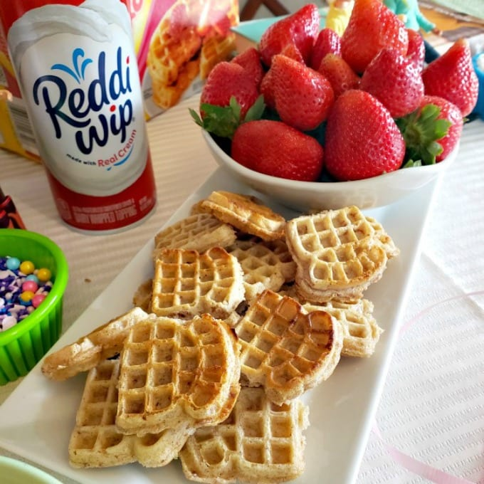 Mini waffles piled on a serving plate next to a bowl of ripe red strawberries and a can of Reddi-Wip.