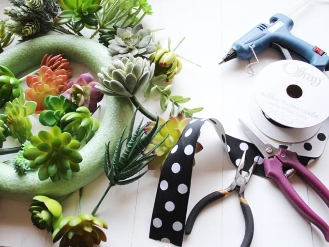 Steps for How to Make a Succulent Wreath, image includes wreath form and faux succulent plants as well as black and white polka dot ribbon, pruning shears and a glue gun.