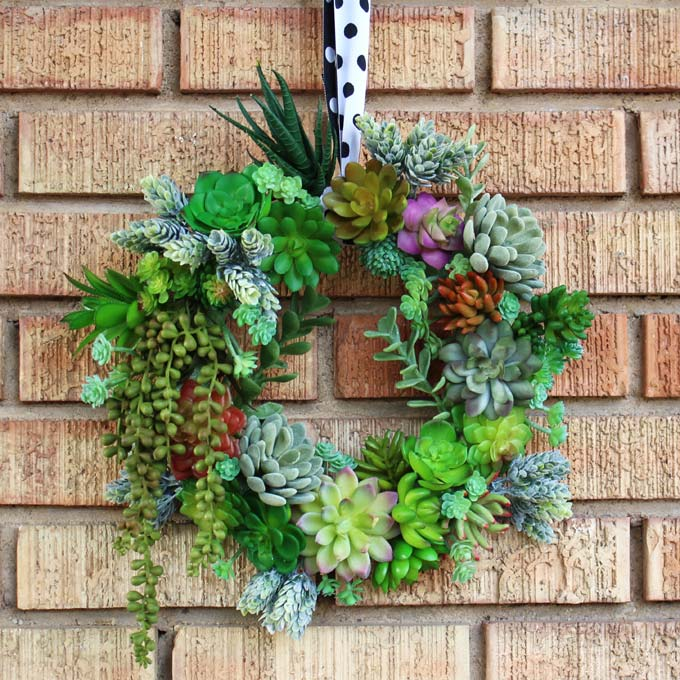 A wreath made with a variety of faux succulents hangs on a brick wall from a black and white polka dot ribbon.