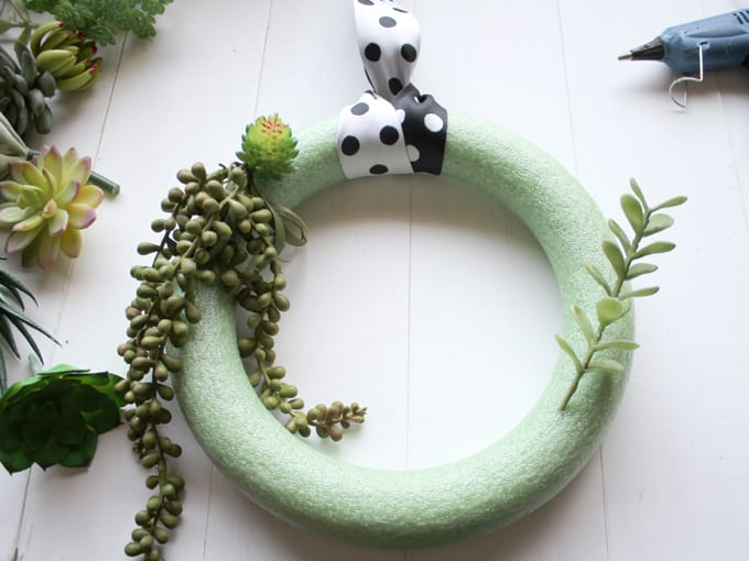 Steps for How to Make a Succulent Wreath, image includes wreath form and faux succulent plants.