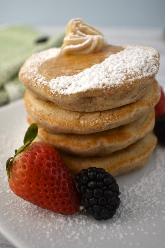 Stack of Silver Dollar Pancakes on a white plate with a dollop of butter and drizzle of maple syrup, garnished with fresh strawberries and black berries