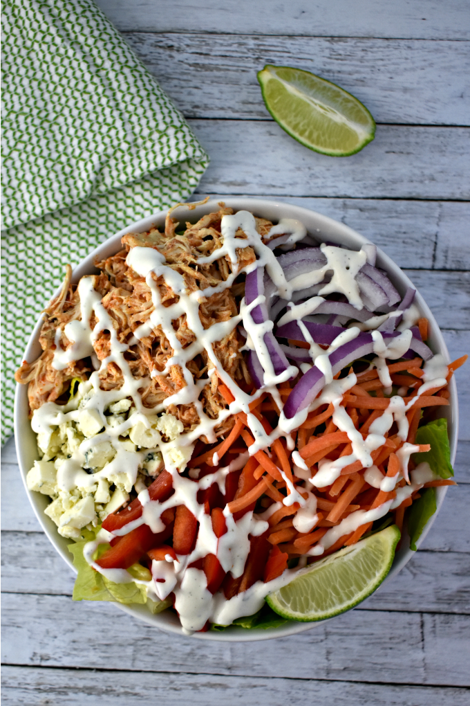 A large white bowl of buffalo chicken salad including crumbled blue cheese, shredded carrots, thinly sliced red onions, chopped tomatoes drizzled with ranch dressing sits on a white table near a wedge of lime and a green and white kitchen towel.