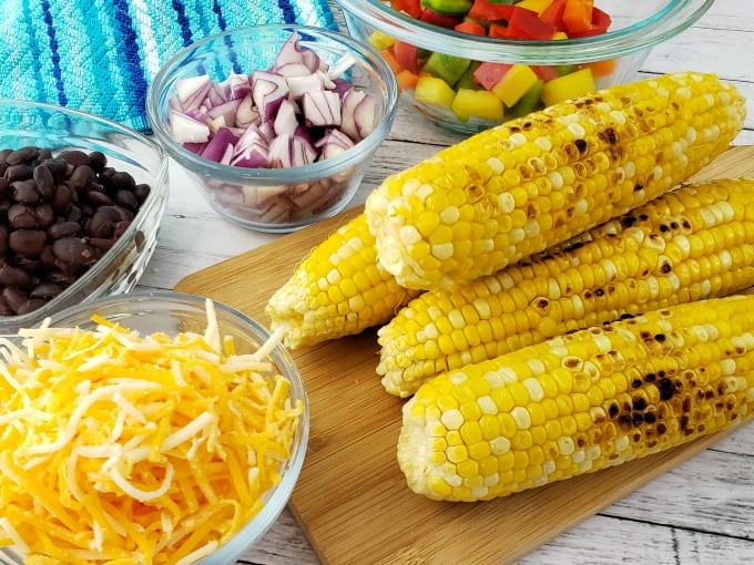 Ingredients for Cornbread Salad including small glass bowls with black beans, chopped red, green, yellow and orange peppers, diced red onion and shredded cheese next to a small cutting board with ears of grilled corn on the cob and a multi-hued blue towel nearby.