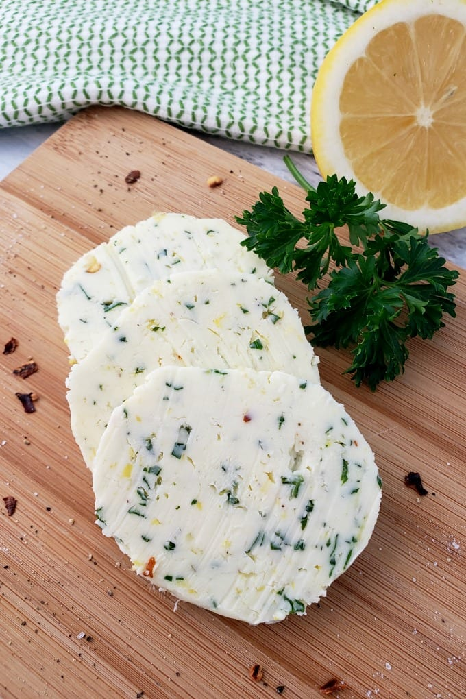 Round slices of Cowboy Butter on a cutting board with a sprig of parsley and a halved lemon.