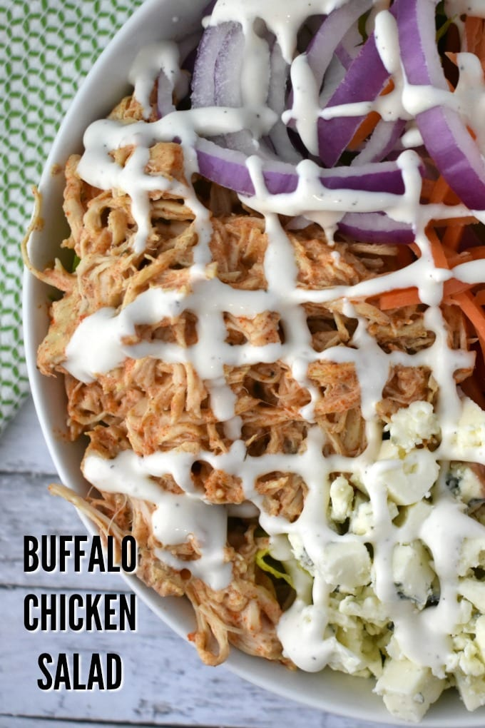 A close of a large white bowl of buffalo chicken salad including crumbled blue cheese, shredded carrots, thinly sliced red onions, chopped tomatoes drizzled with ranch dressing sits on a white table near a green and white kitchen towel.