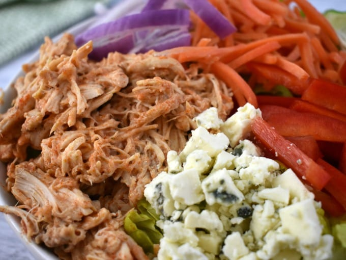 A large white bowl of buffalo chicken salad including crumbled blue cheese, shredded carrots, thinly sliced red onions, chopped tomatoes.