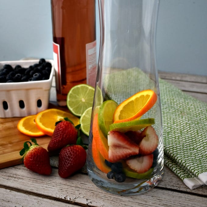 A ceremic berry basket with blueberries, a small cutting board with sliced oranges, limes and strawberries and a carafe with fresh fruit in the bottom and a bottle of pink moscato