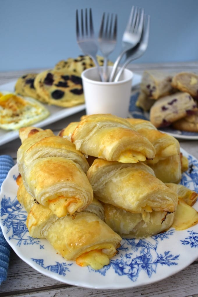 Ham and cheese croissants piled on a blue and white plate in front of a brunch spread.