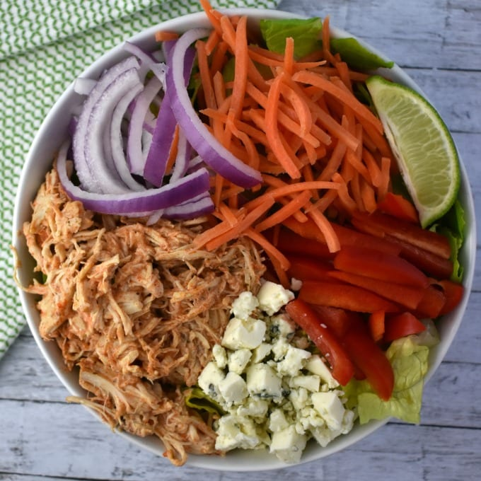 A large white bowl of Buffalo Chicken Salad including slow cooked buffalo chicken, shredded carrots, thinly sliced red onion, sliced red peppers, a wedge of lime and crumbled blue cheese sits on a white table with a green and white kitchen towel.
