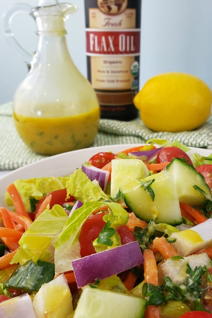 A bowl of garden salad sits on a table with a bottle of Barleans Flax Oil, a cruet of lemon dressing, a whole lemon.