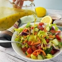 Wide bowl full of garden salad with a lemon in the background. A drizzle of healty lemon dressing is poured on the salad.