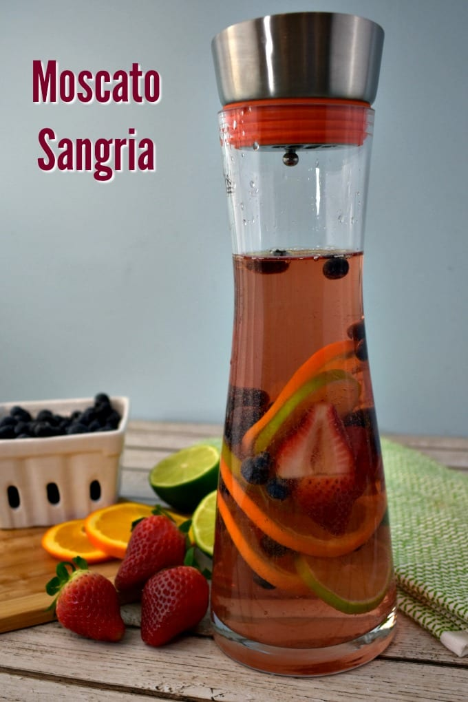 A ceremic berry basket with blueberries, a small utting b oard with sliced oranges, limes and strawberries and a carafe with pink moscato sangria