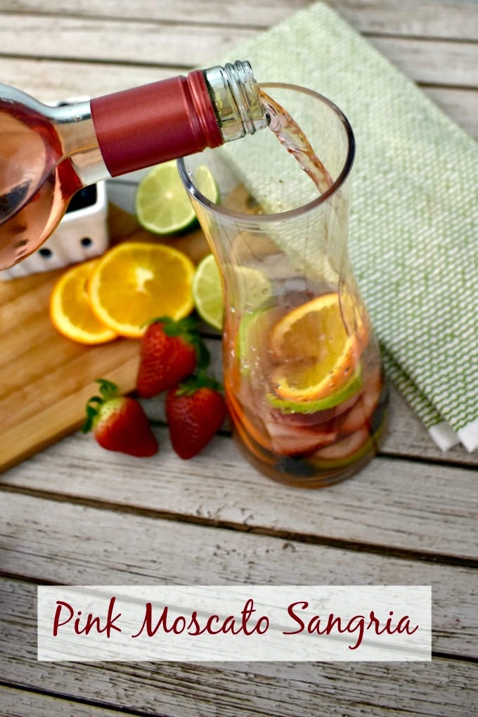 small cutting board with sliced oranges, limes and strawberries and a carafe with pink moscato sangria