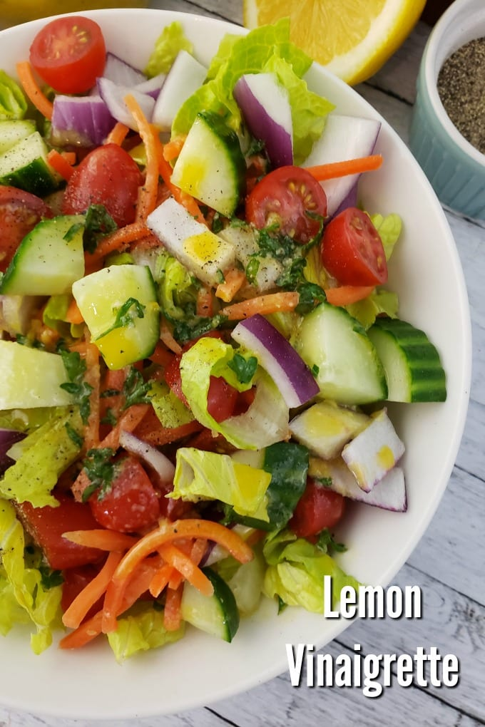 A garden ssalad with cucumbers, tomatoes and carrots drizzled with Lemon Vinaigrette. A halved lemon and ramekins with salt and pepper.