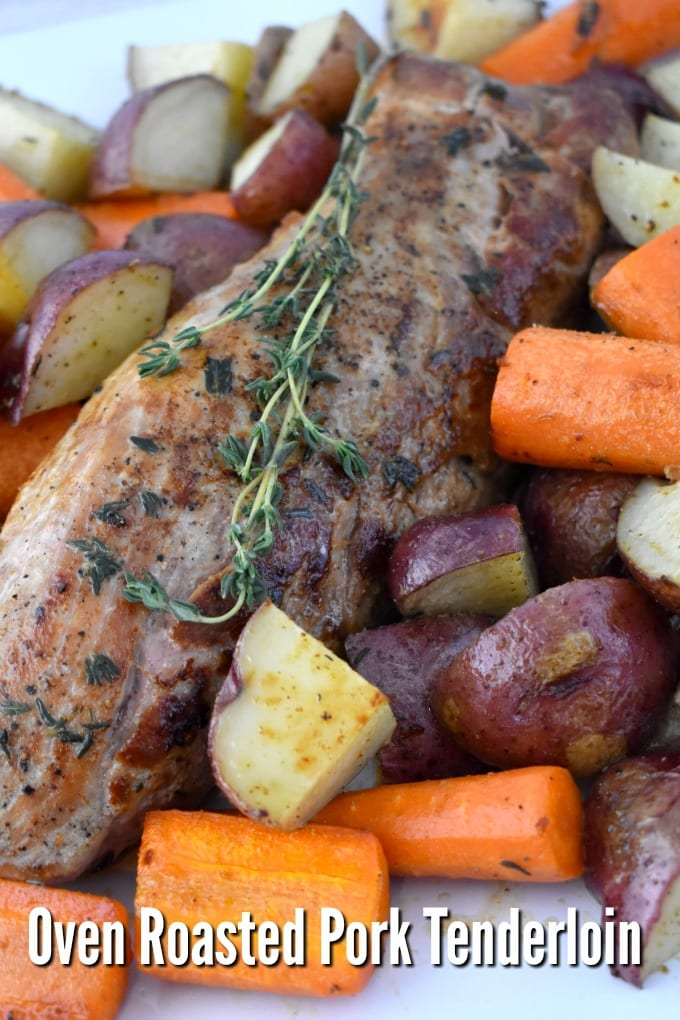 Oven Roasted Pork Tenderloin with potatoes and carrots on a sheet pan with a sprig of fresh thyme