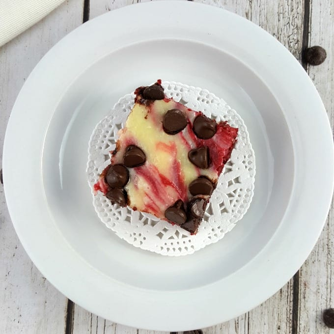 Arial view of a red velvet cheesecake brownie with chocolate chips on a white doily placed on a white plate. The plate is on a white wood background and there is a single chocolate chip on the table next to the plate.