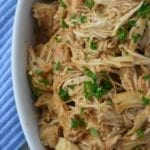Tender spicy slow cooker buffalo chicken piled in a large white bowl, sprinkled with chopped parsley.