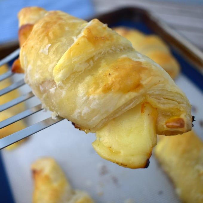 A silver spatula holds a ham and cheese croissant up.