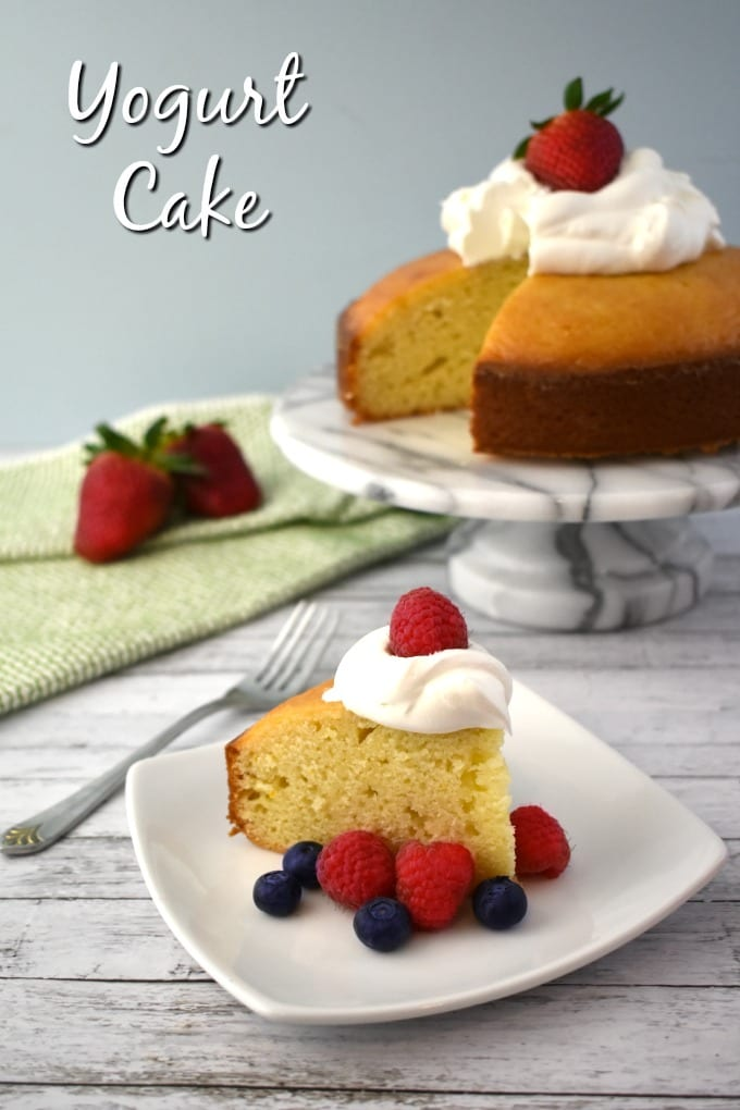 A slice of Yogurt Cake topped with a dollop of whipped cream and surrounded by fresh raspberries and blueberries sits on a white plate. A green and white hand towel can be seen in the background along with a marbled cake tier and a whole Yogurt Cake missing one slice.