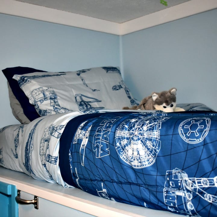 Blue Star Wars bedding on a top bunk bed.
