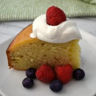 A slice of Yogurt Cake topped with a dollop of whipped cream and surrounded by fresh raspberries and blueberries sits on a white plate. A green and white hand towel can be seen in the background.