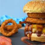 Incredible Cowboy Burger piled high with bacon and crispy onion rings on a sesame seed bun on a slate and wood cutting board. Slices of tomatoes and onion rings can be seen to the left.