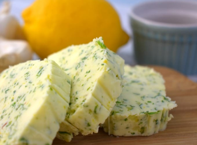 Sliced compound butter on a cutting board with a lemon, garlic and small ramekin in the background. This is used to make the most delicious butter burgers.