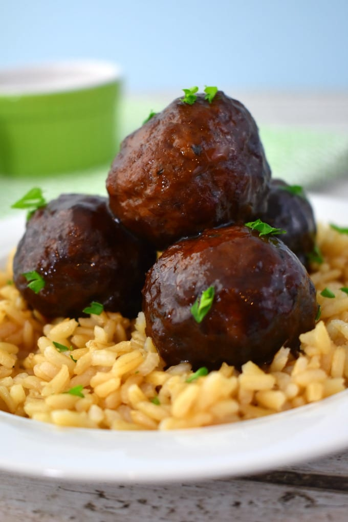 A close up of crockpot jelly meatballs on a bed of brown rice in a white bowl garnished with fresh parsley.