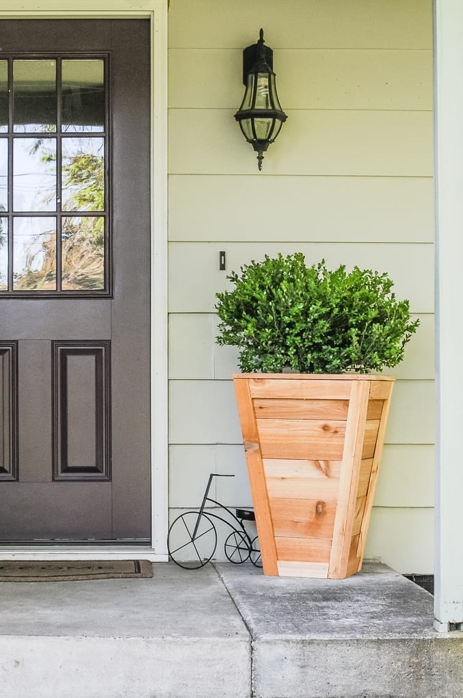 A diy cedar planter box with boxwood planted in it on a front porch next too a brown door.