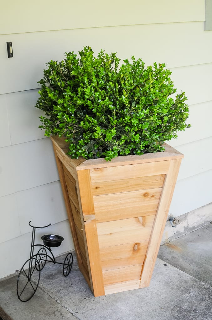 An easy and affordable tutorial for how to build a planter box. Instantly increase curb appeal with a tall, DIY cedar planter box that will last for years! via @jugglingactmama