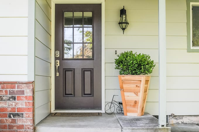 A diy cedar planter box with boxwood planted in it on a front porch next to a brown door.