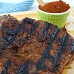Grilled Petite Sirloin Steak on a cutting board. Int he background, a blue towel and a small green ramekin with Cowboy Steak Rub with a wooden spoon.