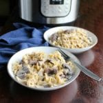two bowls of creamy beef stroganoff with an instant pot in the background