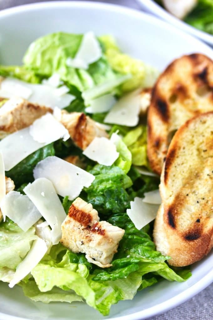 Chicken caesar salad with romaine, grilled chicken, shaved parmesan in a bowl