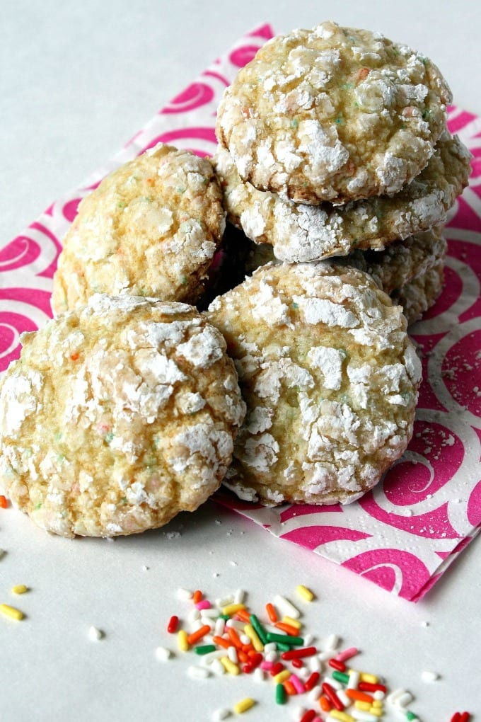 A pile of funfetti crinkle cookies on a pink and white napkins